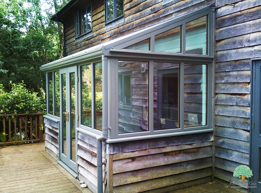 Simple oak lean to conservatory with volcanic ash exterior and oak weatherboard to blend with house